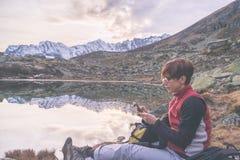 Controllo dello smartphone sulle montagne sceniche Fotografia Stock
