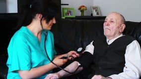 Controllo di pressione sanguigna ad un uomo senior stock footage
