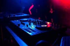 Controllo DJ di musica del regolatore del miscelatore di musica nell'ambito della luce dei riflettori in cabina al night-club Immagine Stock Libera da Diritti