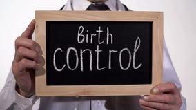 Controlo da natalidade escrito no quadro-negro nas mãos do terapeuta, prevenção da gravidez imagem de stock royalty free