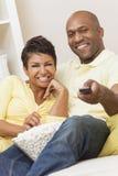 Controlo a distância afro-americano feliz dos pares da mulher Imagens de Stock