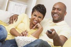 Controlo a distância afro-americano feliz dos pares da mulher Fotografia de Stock