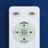 Controlo a distância branco com os botões no fundo azul Fotos de Stock Royalty Free
