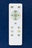 Controlo a distância branco com os botões no fundo azul Imagens de Stock Royalty Free