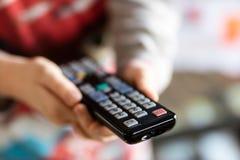 Controlo a distância da tevê realizado no women& x27; mãos de s Canais do interruptor em t imagens de stock