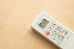 Controlo a distância do condicionador de ar no assoalho de madeira Fotografia de Stock Royalty Free