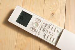 controlo a distância do condicionador de ar no assoalho de madeira imagem de stock