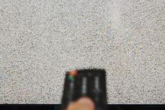 Controlo a distância obscuro da televisão da imprensa da mão para procurar o sinal foto de stock royalty free