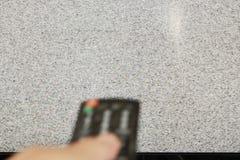 Controlo a distância obscuro da televisão da imprensa da mão para procurar o sinal imagens de stock