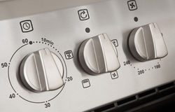 Controls of a modern stainless steel cooker. Close up of controls from a modern stainless steel oven Stock Photo