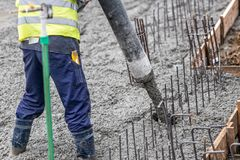 Contruction工作者倾吐的混凝土,指挥泵浦管 免版税库存照片