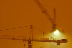 Contruction cranes at night. Two contruction cranes over a construction at night Royalty Free Stock Photography