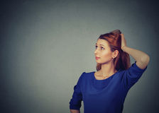 Contused thinking woman bewildered scratching her head seeks solution. Young woman looking up Royalty Free Stock Images