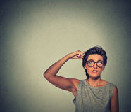 Contused thinking woman with glasses bewildered scratching her head Royalty Free Stock Photos