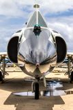 Convair F-102 Delta Dagger. Frontal view of F-102 aircraft, intakes, wheels, sky reflection in puddle royalty free stock photos