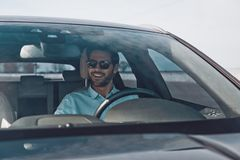 Convenience way to travel. Handsome young man smiling while driving a status car stock photos