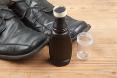 Convenient liquid shoe polish with worn out shoes on wooden plat Stock Image