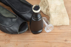Convenient liquid shoe polish with worn out shoes on wooden plat Royalty Free Stock Photos