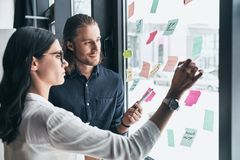 Convenient organization. Two young colleagues in smart casual we. Ar using adhesive notes on the window while working together in the office Stock Photography