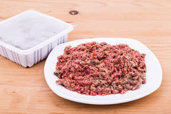Convenient packaged minced raw meat dog food on plate. Convenient packaged delicious and nutritious minced raw meat dog food on plate Stock Images