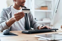 Convenient shopping. Close up of young man in casual clothing making a purchase online while spending time at home stock image