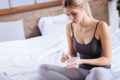Young woman taking medication from pill organizer. Convenient storage. Beautiful slender woman sitting on the bed and taking pills from a pill organizer Royalty Free Stock Image