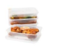 Convenient but unhealthy disposable plastic lunch boxes with meals. Convenient but unhealthy disposable plastic lunch boxes with take away meal on white stock images