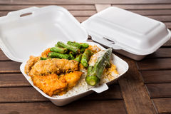 Convenient but unhealthy polystyrene lunch boxes with take away. Meal on wooden table Stock Photo
