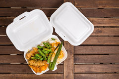 Convenient but unhealthy polystyrene lunch boxes with take away. Meal on wooden table Stock Image