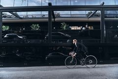 Convenient way to travel. Handsome young man in full suit hurrying to work while cycling outdoors royalty free stock photo