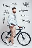 Convenient way to travel. Full length of a modern looking man with beard pulling his bicycle while standing against grey. Background with hand drawn doodles on royalty free stock photos