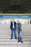 Convention Center attendees. Two attendees of a congress at a trade fair posing on the steps leading to the front entrance of the convention center Stock Photography