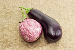 Conventional eggplant and graffiti eggplant on a sackcloth Stock Photo