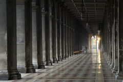 Convergence. Long hallway and pillars with bright light at the end Stock Image