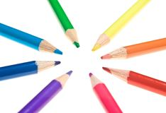 Converging Coloured Pencils. Eight coloured pencils pointing towards the same spot, isolated on white Stock Photo