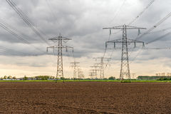 Converging high voltage cables and steel pylons in an agricultur Stock Photography
