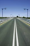 Converging lines of road on bridge. Converging white and yellow lines of road on bridge in Seville Spain on a sunny day Royalty Free Stock Image