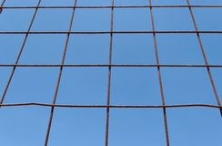 Converging view of rusty lattice on sky background Stock Photography
