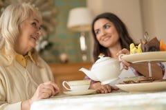 Conversação agradável entre a mãe e a filha superiores sobre o copo do chá imagem de stock royalty free
