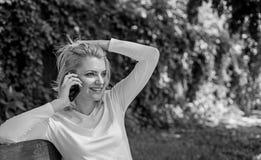 Conversação agradável Fundo de sorriso louro da natureza do verde do smartphone da conversa da cara da menina Mulher que tem agra imagem de stock royalty free