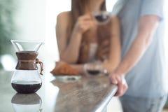 Conversação amigável sobre um café da manhã: uma posição dos pares no contador de cozinha, café bebendo fotografia de stock