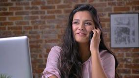 Conversação de relaxamento sobre o telefone da mulher agradável caucasiano que está apreciando seu tempo que se senta no desktop, filme