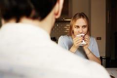 Conversação do homem seguro e da mulher loura nova em casa fotografia de stock royalty free