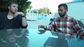 Conversação dos executivos em uma atmosfera fácil em uma tabela video estoque