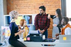 Conversação entre trabalhadores de escritório da raça misturada na roupa ocasional fotografia de stock royalty free