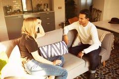 Conversação no sofá do homem seguro e do apartamento louro novo da mulher em casa fotos de stock
