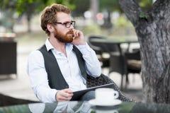 Conversação telefônica principal no café exterior foto de stock