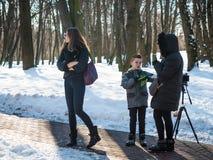 Conversa adorável do modelo do menino com o produtor no parque do inverno, de bastidores imagem de stock