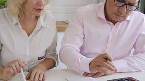 Conversa americana do homem de negócios e da mulher durante o trabalho com relatório em iluminar a sala video estoque