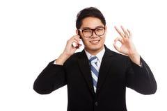 Conversa asiática do sinal da APROVAÇÃO da mostra do sorriso do homem de negócios no telefone celular Imagens de Stock Royalty Free